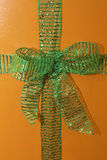 Wrappings. Orange box tied with green, glitter ribbon Royalty Free Stock Photos