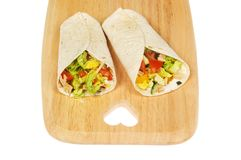 Wraps on a board. Chicken and salad wraps on a board with a heart shaped cutout isolated against white stock photography