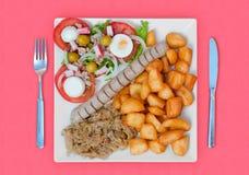 Wratwurst met zuurkoolsalade en aardappels stock afbeeldingen