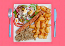 Wratwurst with sauerkraut salad and potatoes. A combined food with wratwurst with sauerkraut salad and potatoes with fork and knife Royalty Free Stock Images