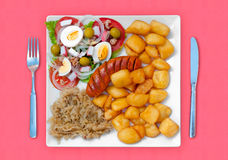 Wratwurst with sauerkraut salad and potatoes. A combined food with wratwurst with sauerkraut salad and potatoes with fork and knife Royalty Free Stock Image