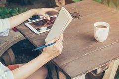 Wręcza kobiety używa pastylkę i trzymający notatnika na stołowym drewnie przy co Obrazy Royalty Free
