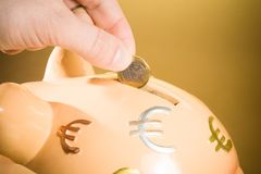 Wręcza wkładać monetę w prosiątko banka i save pieniądze, pojęcie dla biznesowego Obraz Royalty Free