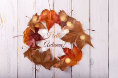 Wreath of autumn leaves. On white rustic wooden background with Hello autumn hand lettering calligrapy text, overhead view Royalty Free Stock Image