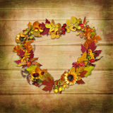 Wreath of autumn leaves on a wooden background Stock Photos