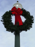 Wreath & Bow. Green Christmas wreath with red bow on street lamp Stock Photos