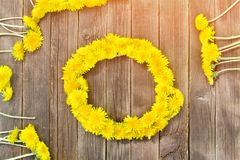 Wreath of dandelions on a wooden table. Summer.  Stock Images