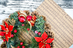 Wreath fir cones, sheet music Christmas songs concept of preparing for the holidays, turquoise shabby wooden table background. pla Stock Image