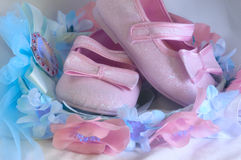 The wreath of flowers and baby shoes. The composiyion with the wreath with flowers and pink baby shining shoes Stock Photos