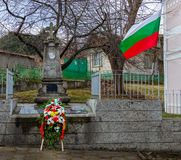 Wreath of flowers at the cenotaph. Bulgarian independence day, a wreath of flowers laid at the village cenotaph next to the national flag in memory of the fallen royalty free stock photography