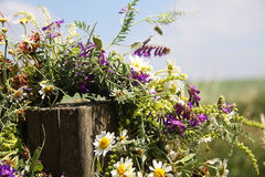 Wreath of flowers hanging on a wooden stick on a wild field Royalty Free Stock Photography
