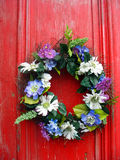 Wreath of flowers on red door Stock Photos