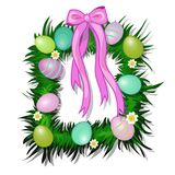 Wreath of grass and flowers with Easter colored eggs and pink bow with ribbon. Symbol and decoration for holiday Stock Image