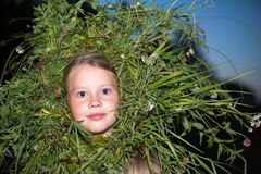 A wreath of green grass on the girl`s head royalty free stock photos