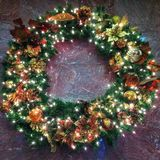 Wreath. With lights, pine cones, and decorations against a marble wall Stock Image