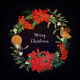 Wreath made of bunches of rowan berries, branches of coniferous trees, poinsettia plant, mistletoe, oranges, star anise. And decorated with light garland Royalty Free Stock Photography