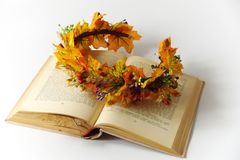 Autumn wreath of autumn leaves. Do it yourself on the instructions.A wreath of leaf fall on the old book. A wreath of maple leaves for the autumn holidays royalty free stock photo