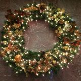 Wreath Muted Colors. Wreath with lights, pine cones, and decorations against a marble wall Stock Photos