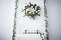 A wreath of roses hangs over the fireplace stock image