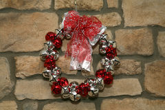 Wreath on stone wall. Holiday wreath made from silver and red bells hung on stone wall Royalty Free Stock Image