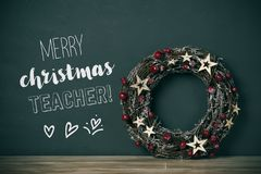 Wreath and text merry christmas teacher. A nice christmas wreath with red fruits and golden stars, and the text merry christmas teacher in a green chalkboard stock images