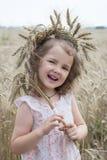 Wreath of wheat on little girl head. Beautiful field & nature stock image