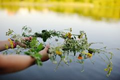 Wreath of wild flowers in children`s hands. Close-up on the background of the river Stock Photo