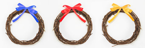 Wreath woven from the branches with colorful ribbon, on white wall Royalty Free Stock Image