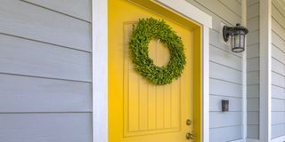 Wreath on yellow front door and a lamp on a wall. A simple wreath made out of green leaves hangs on the bright yellow front door. A lamp is mounted on the royalty free stock photos