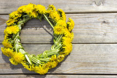 Wreath of yellow spring flowers - dandelions on a wooden background Stock Images
