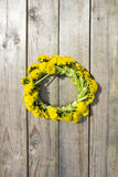 Wreath of yellow spring flowers - dandelions on a wooden background, romantic spring summer Royalty Free Stock Photography