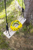 Wreath of yellow spring flowers - dandelions  On a wooden swing in the garden Stock Images