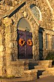Wreaths on church doors. Autumn colored wreaths on purple church doors Royalty Free Stock Image