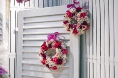 Wreaths of flowers at the door. Interior shot of a rustic door with a lovely wreaths. Shabby chic Stock Photo