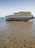 Wreck of boat on beach. Wreck of an abandoned wooden boat on a beach Stock Photos