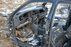 Wreck of a devastated car on a meadow. Disassembled car skeleton royalty free stock image