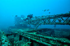 Wreck and Diver. Woman scuba diver swims along a shipwreck underwater at Grenada in the Carribean Ocean royalty free stock photo