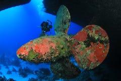 Wreck Diving. Scuba Diver explores propeller of ship wreck stock photo