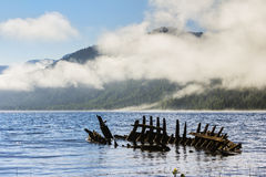 Wreck of old wooden ship on the Lake Teletsky in mountains. Stock Photos