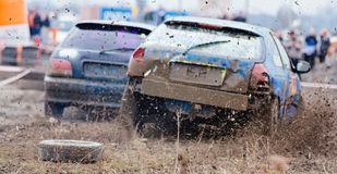 Wreck scrap cars dirt race. Selective focus on splashing mud Stock Image