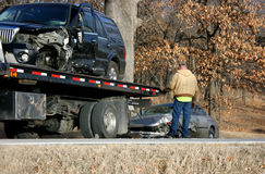 Wreck SUV Sedan Tow Truck. A Ford Lincoln Navigator loaded onto a tow truck after a collision.  Small sedan also being loaded by the tow truck driver Royalty Free Stock Photography
