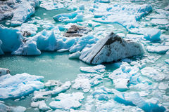 The wreckage of the glacier floats on the surface of the water. Shevelev. The wreckage of the glacier floats on the surface of the water. The uneven surface of Royalty Free Stock Image