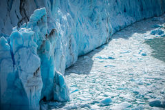 The wreckage of the glacier floats in the water near the iceberg. Shevelev. The wreckage of the glacier floats in the water near the iceberg. The uneven surface Stock Image