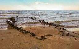 Wreckage of an old wooden boat. Wreckage of an old wooden fishing boat on the Baltic Sea coast, Latvia Royalty Free Stock Images