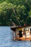 Wrecked a abandonné le bateau sur une rivière Photographie stock