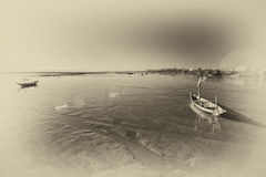Wrecked boat at receding shore Royalty Free Stock Images