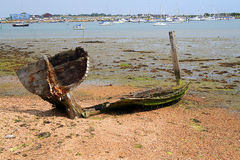 A wrecked boat. On the shore with a whale like tail stock photography