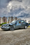 Wrecked car outside city- HDR. An abandoned, wrecked car parked in a lot outside of an urban area royalty free stock image