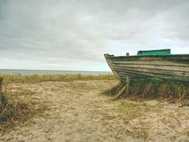 Wrecked fishing boat on old dry grass. Abandoned wooden ship with damaged engine Stock Images