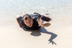 Wrecked man on the coastline. Stretches out his hand for help Stock Photo